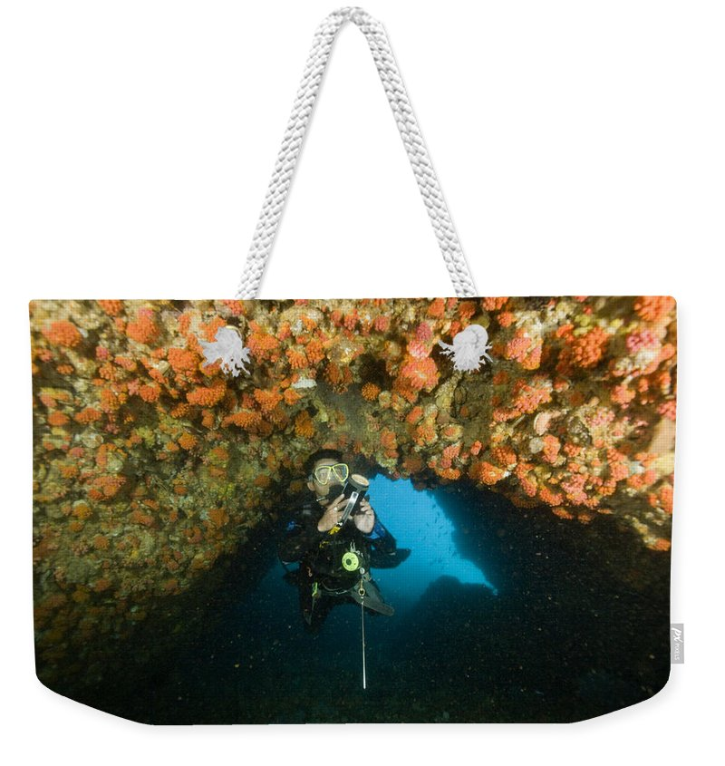 Diving Gear Weekender Tote Bag featuring the photograph A Diver Explores A Cavern With Orange by Tim Laman
