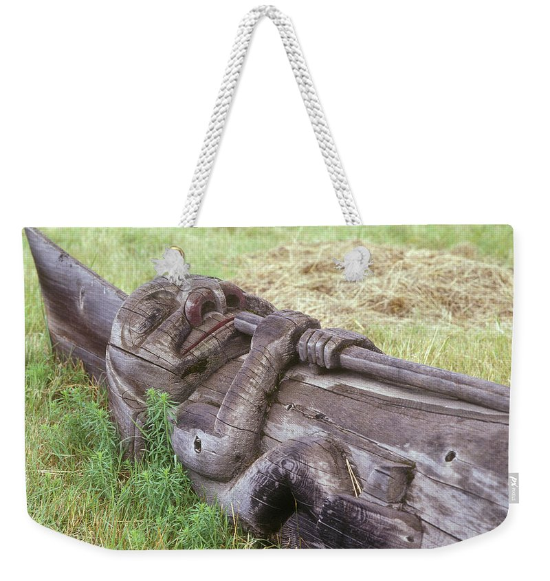 Color Image Weekender Tote Bag featuring the photograph A Fallen Wooden Totem Pole Lies by Stephen Sharnoff