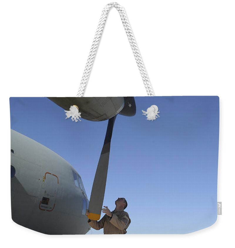Afghanistan Weekender Tote Bag featuring the photograph A Flight Engineer Performs A Pre-flight by Stocktrek Images