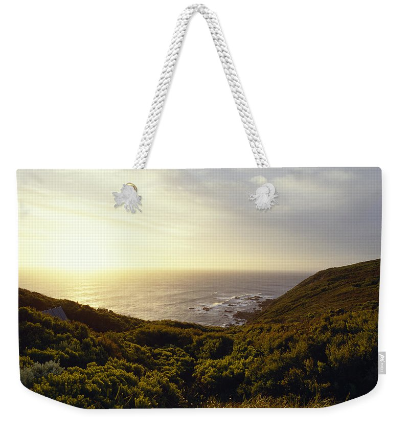 Coastal Weekender Tote Bag featuring the photograph A Hidden Roof Top Overlooks A Scenic by Jason Edwards