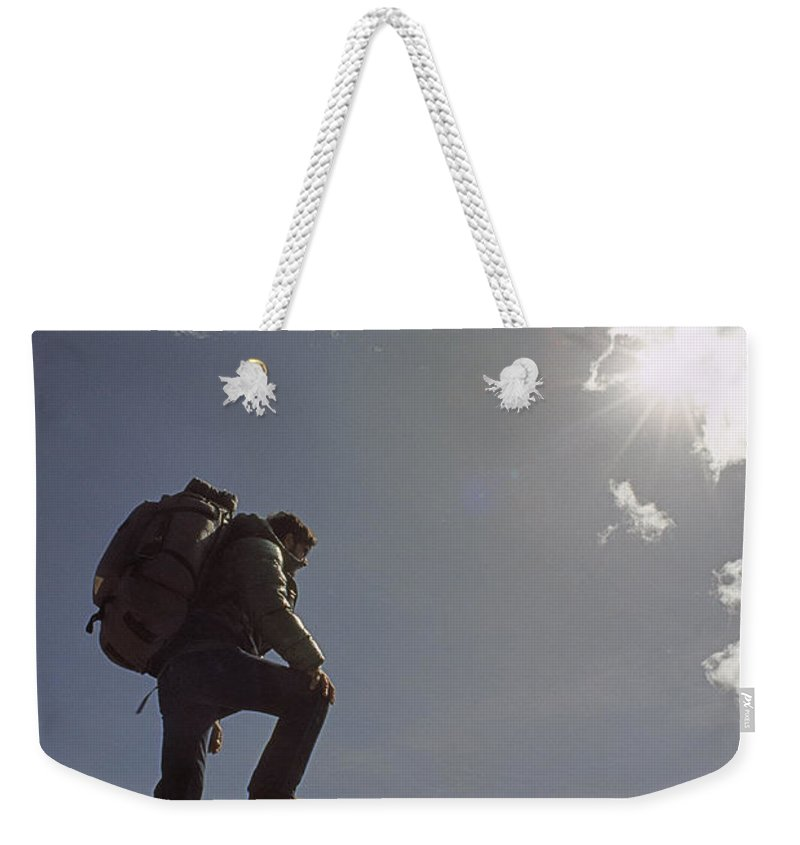 Sierra Nevada Weekender Tote Bag featuring the photograph A Hiker Rests Atop A Huge Granite by Gordon Wiltsie