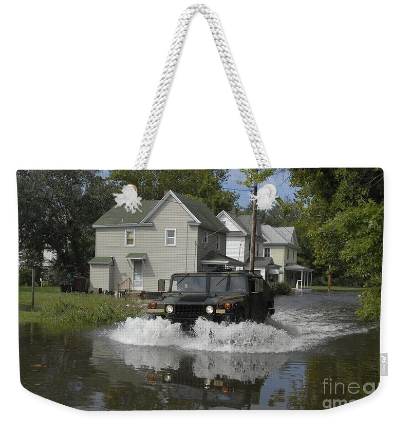 Suburb Weekender Tote Bag featuring the photograph A Humvee Drives Through The Floodwaters by Stocktrek Images