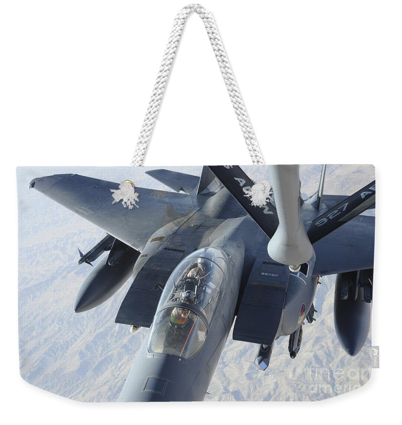 Kc-135 Stratotanker Weekender Tote Bag featuring the photograph A Kc-135 Stratotanker Refuels An F-15e by Stocktrek Images