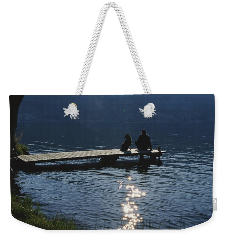 North America Weekender Tote Bag featuring the photograph A Man And His Dog On A Lake Skaha Dock by Mark Cosslett