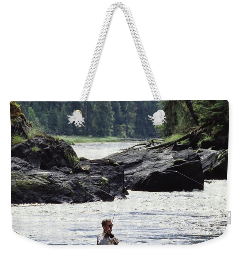Fishing And Fishermen Weekender Tote Bag featuring the photograph A Man Fishes For Cutthroat Trout In An by Bill Curtsinger