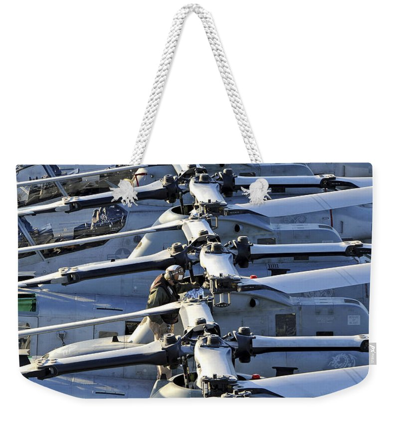 Military Weekender Tote Bag featuring the photograph A Marine Conducts Maintenance On An by Stocktrek Images
