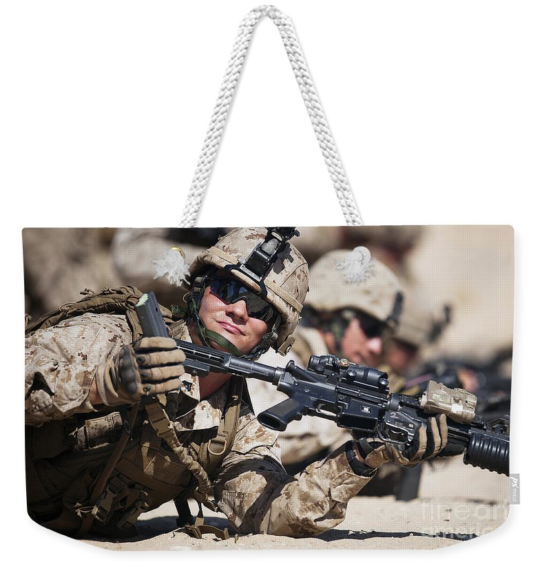 Afghanistan Weekender Tote Bag featuring the photograph A Marine Shows His Cleared Weapon by