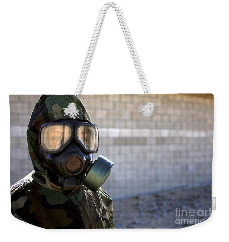 Protective Clothing Weekender Tote Bag featuring the photograph A Marine Wearing A Gas Mask by Stocktrek Images