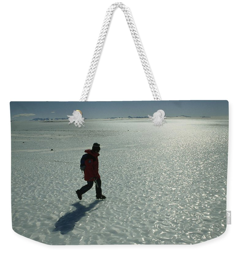 Color Image Weekender Tote Bag featuring the photograph A Mountaineer Crosses A Wind-scoured by Gordon Wiltsie