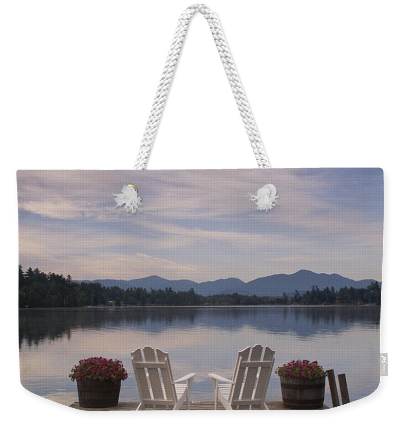 Structures Weekender Tote Bag featuring the photograph A Pair Of Adirondack Chairs On A Dock by Michael Melford