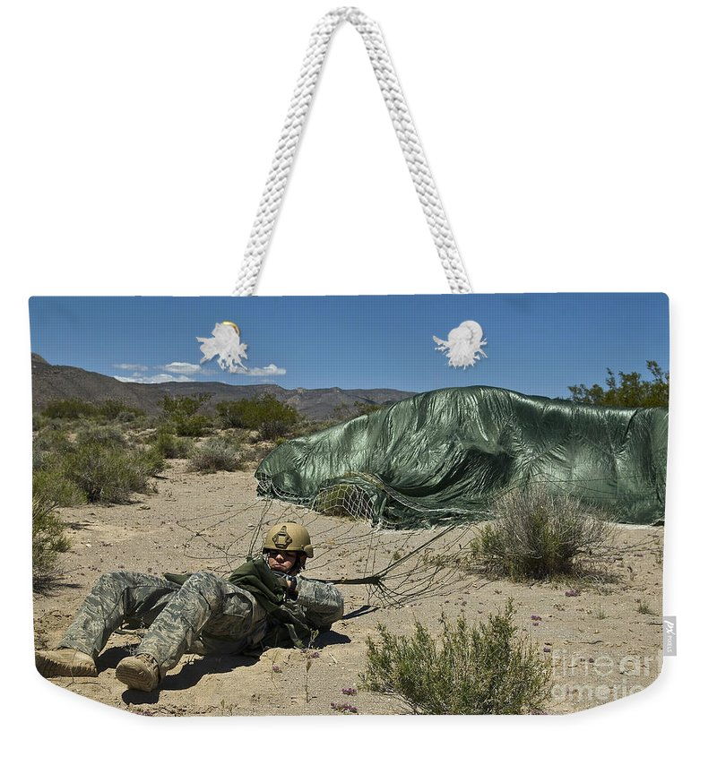 Parachuting Weekender Tote Bag featuring the photograph A Paratrooper Recovers After Landing by Stocktrek Images