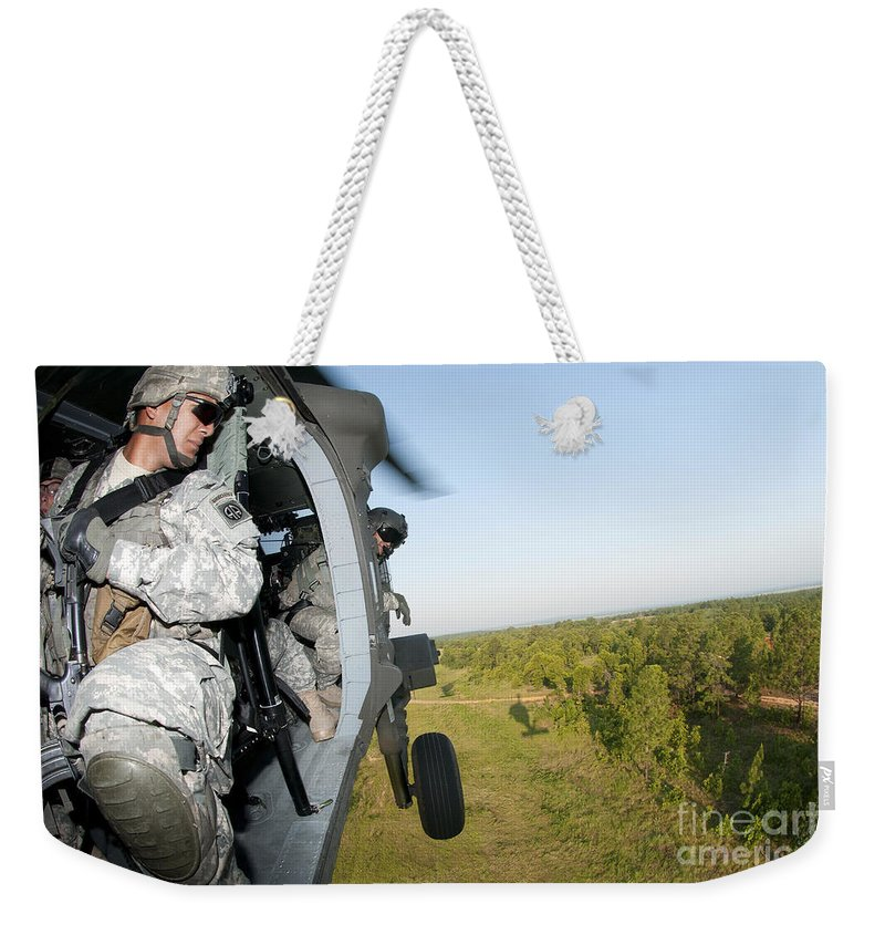 Air Assault Weekender Tote Bag featuring the photograph A Platoon Sergeant Prepares To Land by Stocktrek Images