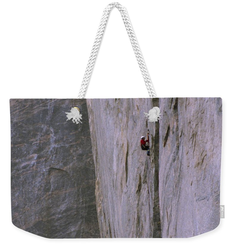 Great Sail Peak Weekender Tote Bag featuring the photograph A Rock Climber Clings To An Overhang by Gordon Wiltsie