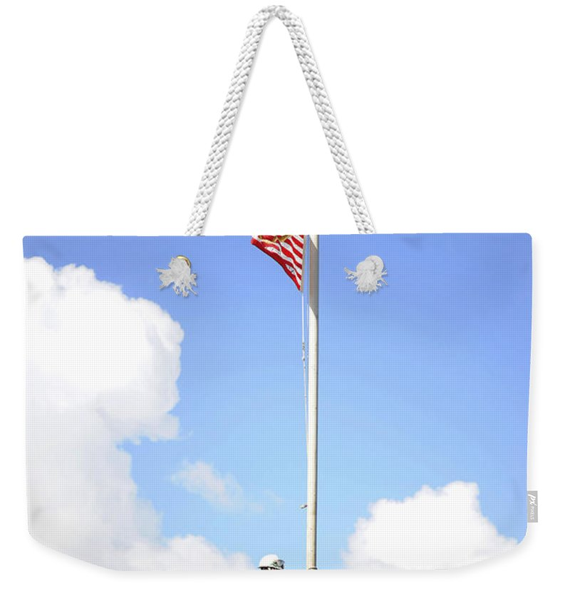 Uss Monterey Weekender Tote Bag featuring the photograph A Sailor Raises The First Navy Jack by Stocktrek Images