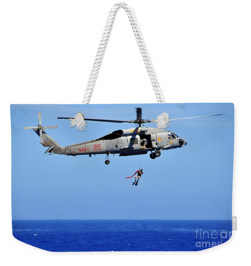 Southern Seas 2010 Weekender Tote Bag featuring the photograph A Search And Rescue Swimmer Is Lowered by Stocktrek Images