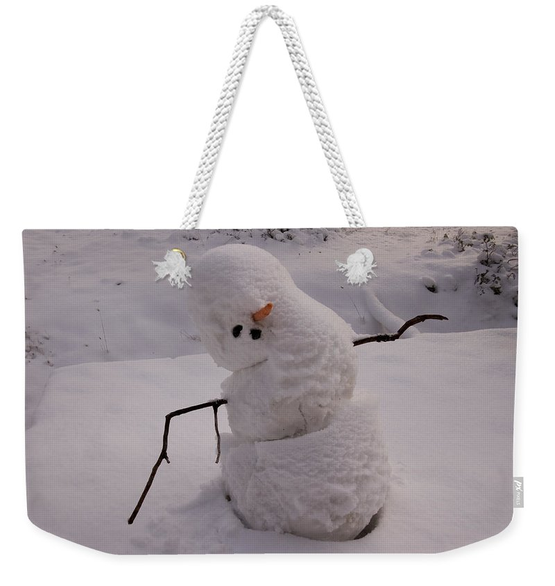 Nobody Weekender Tote Bag featuring the photograph A Snowman Sitting In The Snow by Phil Schermeister