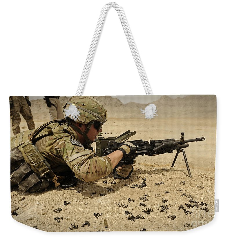 Provincial Reconstruction Team Weekender Tote Bag featuring the photograph A Soldier Clears The Mk-48 Machine Gun by Stocktrek Images