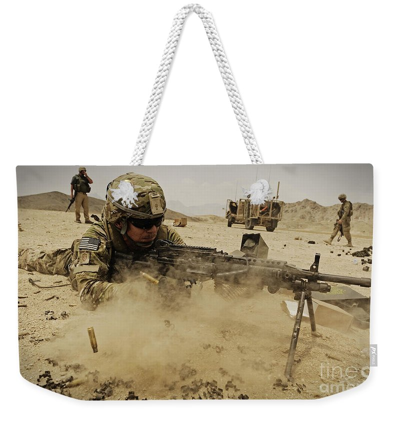 M203 Weekender Tote Bag featuring the photograph A Soldier Firing His Mk-48 Machine Gun by Stocktrek Images