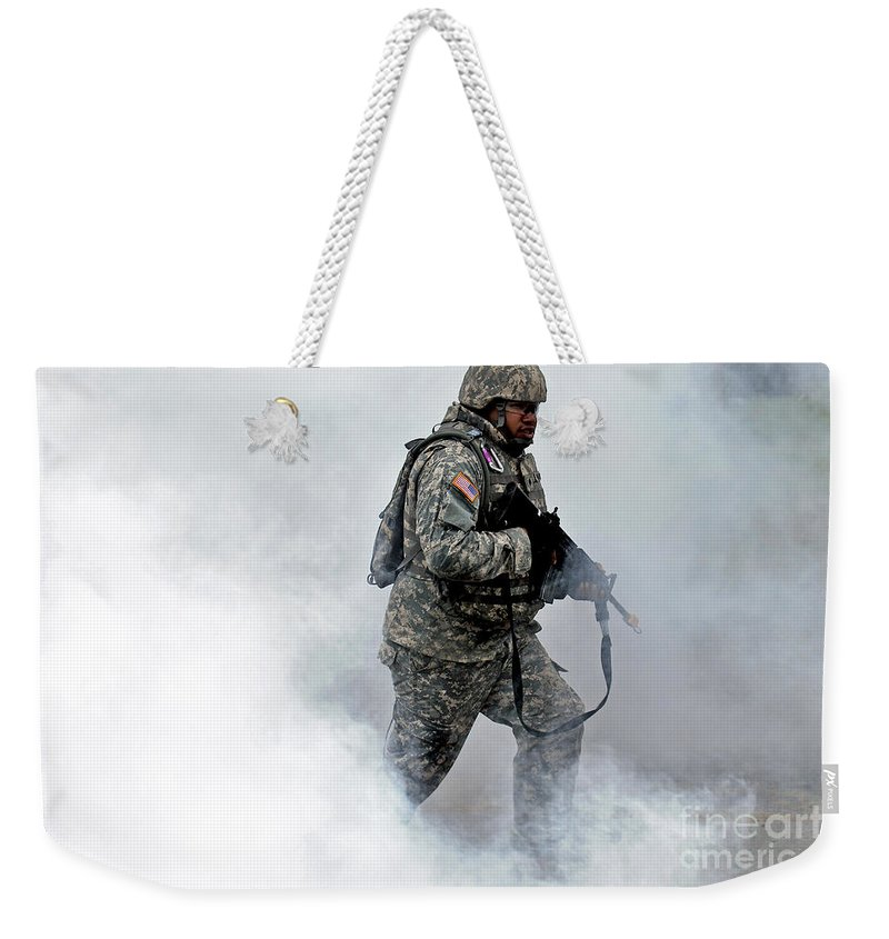Conflict Weekender Tote Bag featuring the photograph A Soldier Races Through A Smoke Screen by Stocktrek Images
