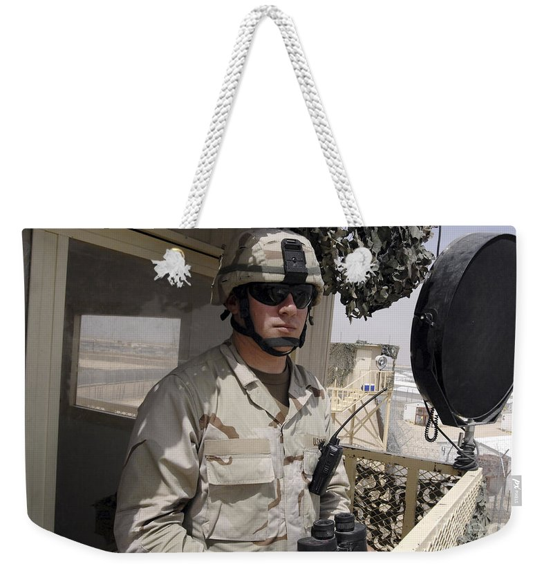 Military Base Weekender Tote Bag featuring the photograph A Soldier Stands Watch At The Camp by Stocktrek Images