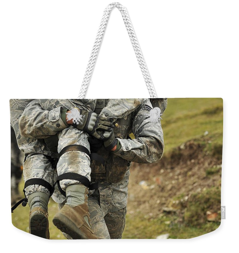 Military Weekender Tote Bag featuring the photograph A Soldier Transports A Fellow Wounded by Stocktrek Images