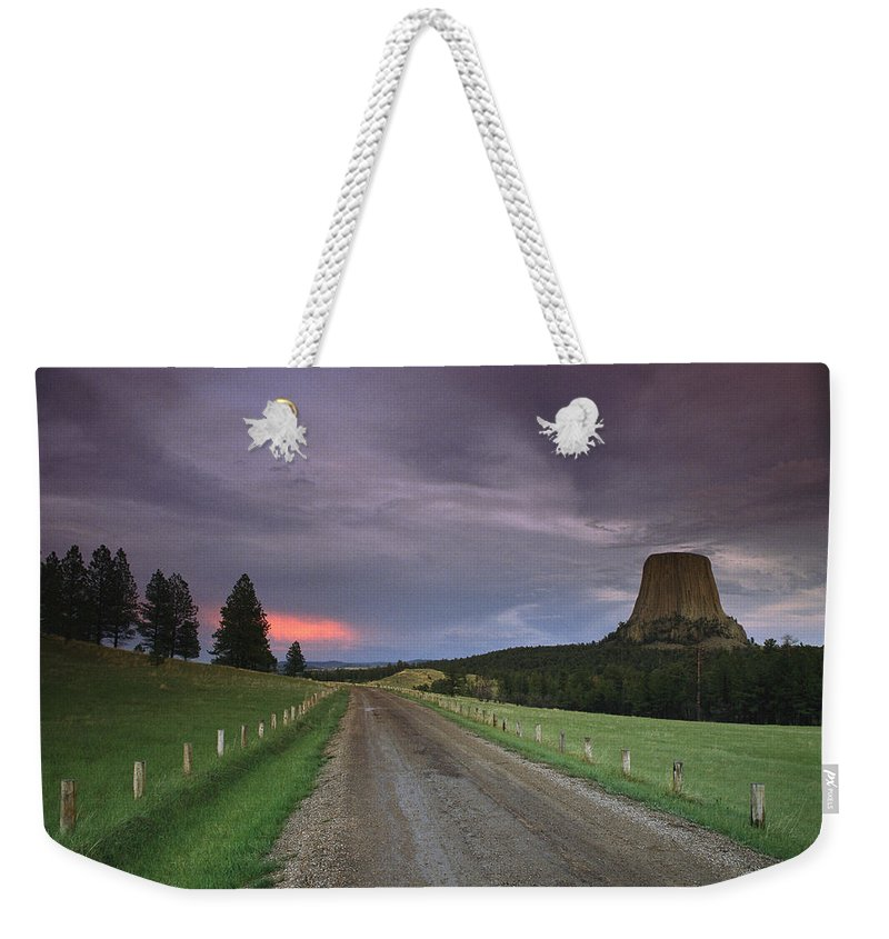 North America Weekender Tote Bag featuring the photograph A Twilight View Down A Dirt Road by Bill Hatcher
