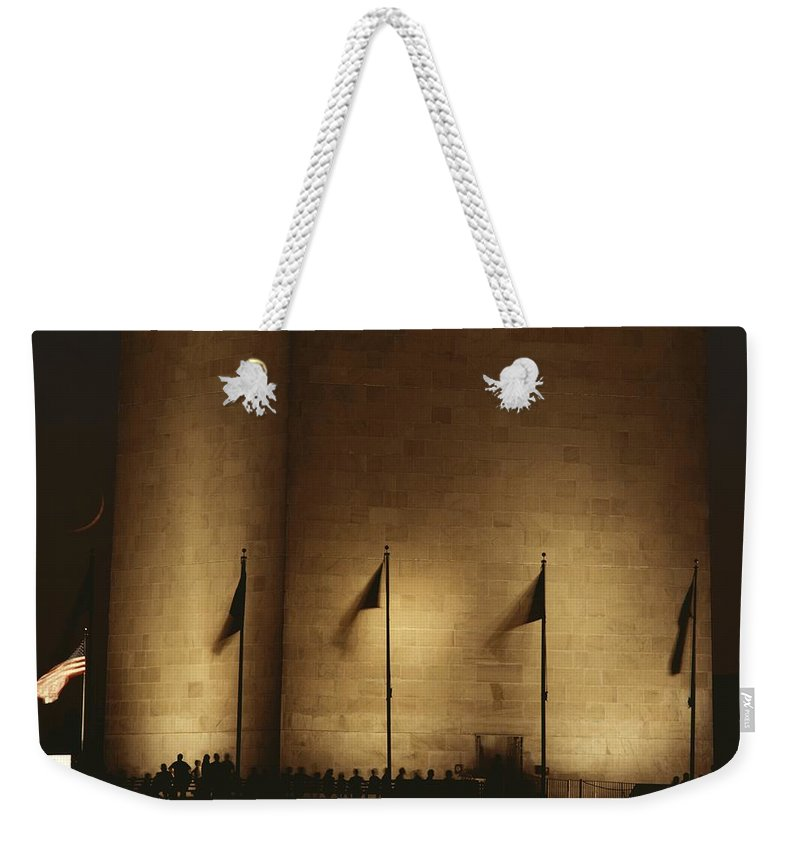 Flags Weekender Tote Bag featuring the photograph A Twilight View Of American Flags by Karen Kasmauski