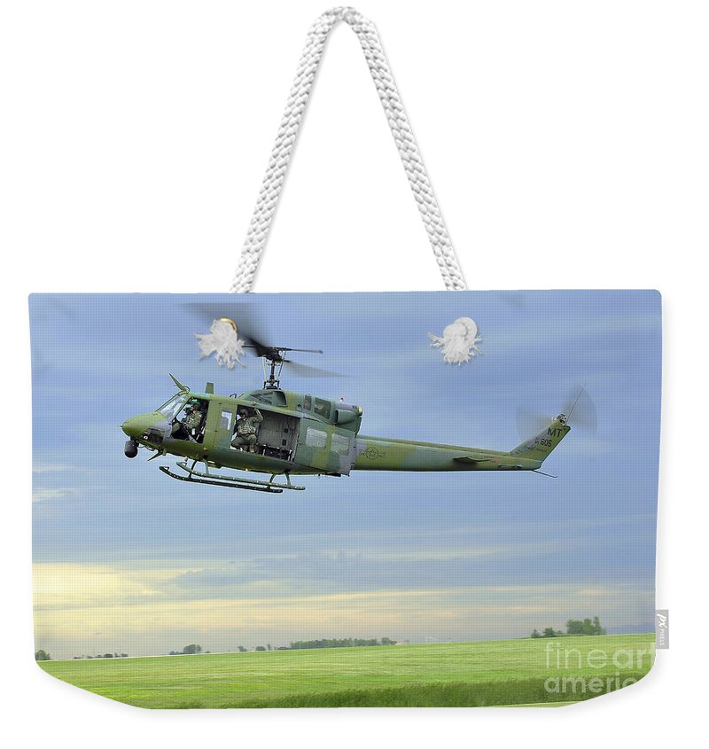 Minot Air Force Base Weekender Tote Bag featuring the photograph A Uh-1n Huey Helicopter Prepares by Stocktrek Images