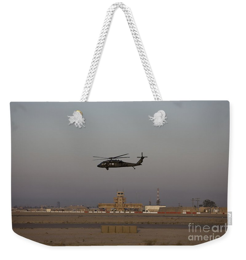 Aircraft Weekender Tote Bag featuring the photograph A Uh-60 Blackhawk Helicopter Flies by Terry Moore