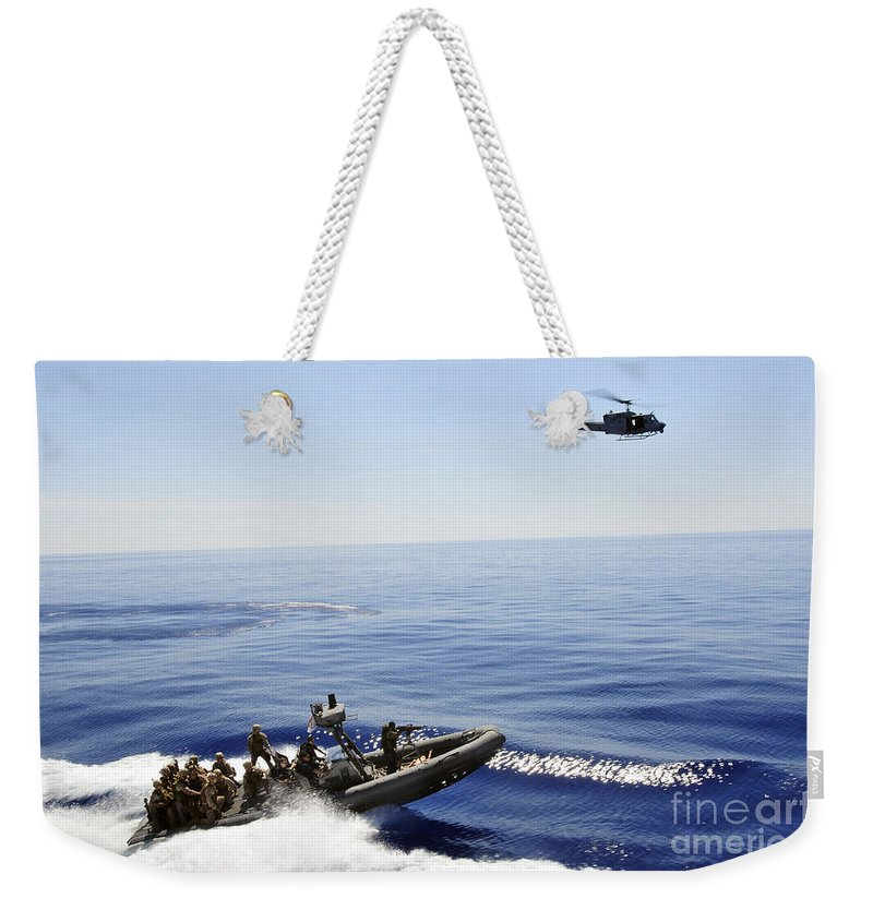 Chasing Weekender Tote Bag featuring the photograph A U.s. Navy Uh-1n Huey Helicopter by Stocktrek Images