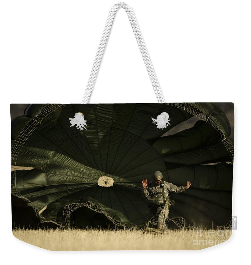 Military Weekender Tote Bag featuring the photograph A U.s. Soldier Collapses His Parachute by Stocktrek Images