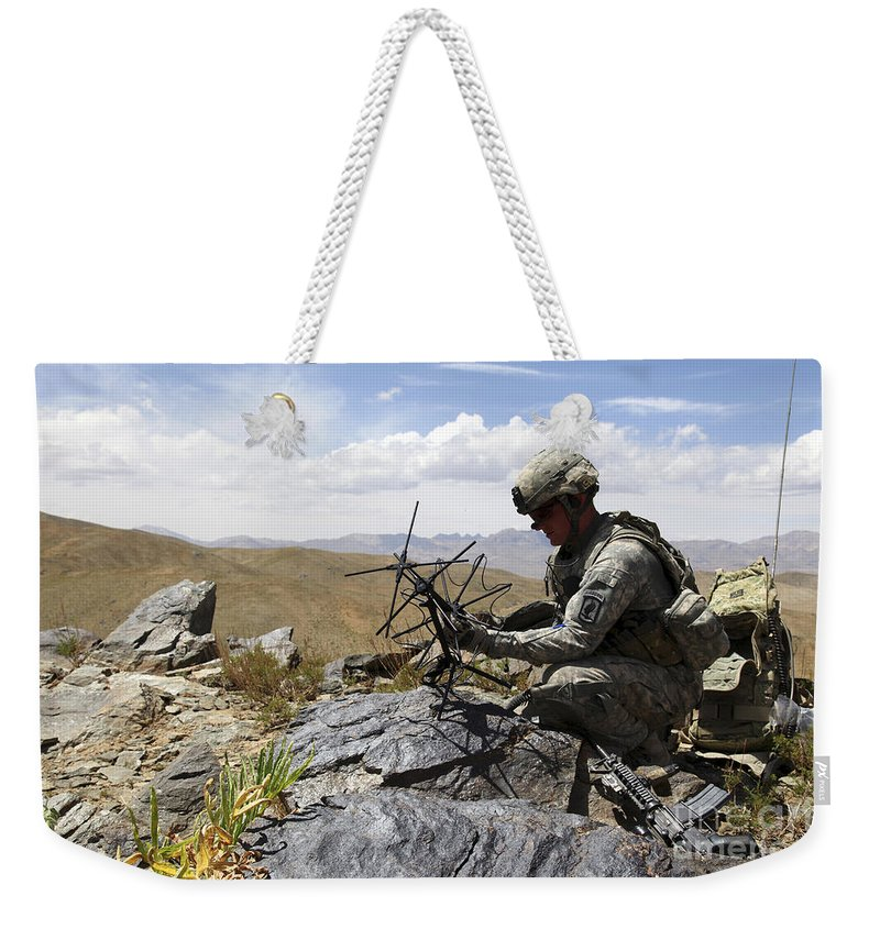 Afghanistan Weekender Tote Bag featuring the photograph A U.s. Soldier Sets Up A Portable by Stocktrek Images