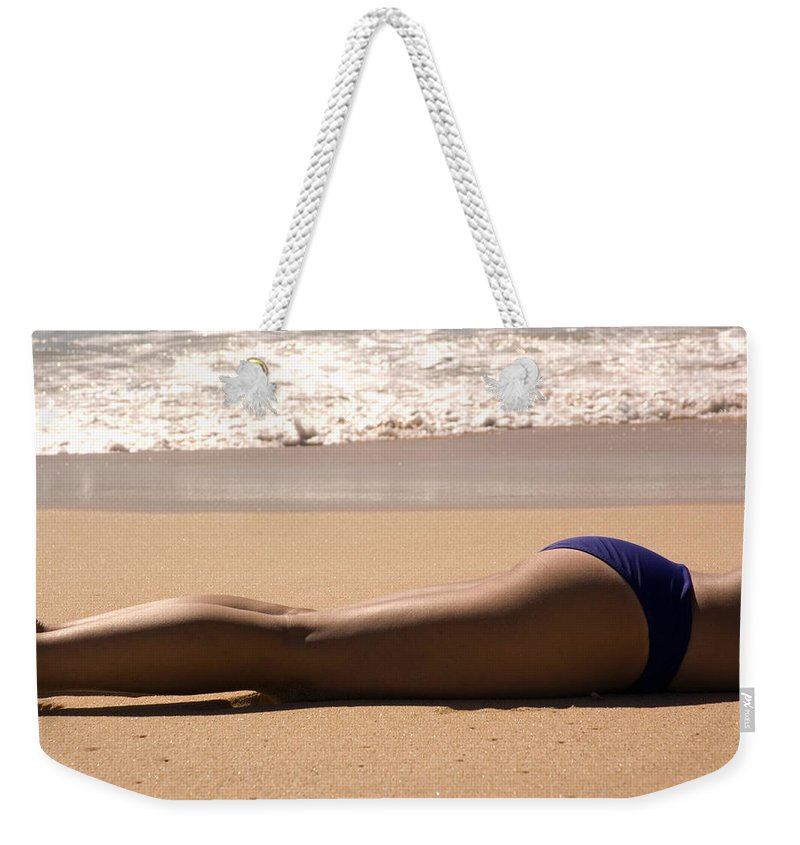 Sandy Beach Weekender Tote Bag featuring the photograph A Woman Sunbathes On The Beach by Stacy Gold