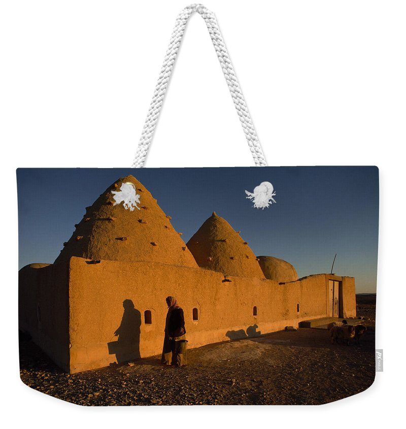 Color Image Weekender Tote Bag featuring the photograph A Woman Walks Past A Sunlit Mud Brick by James L. Stanfield