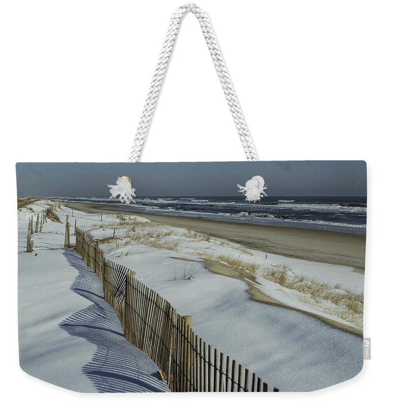 North America Weekender Tote Bag featuring the photograph A Wooden Fence Casts A Shadow by Medford Taylor