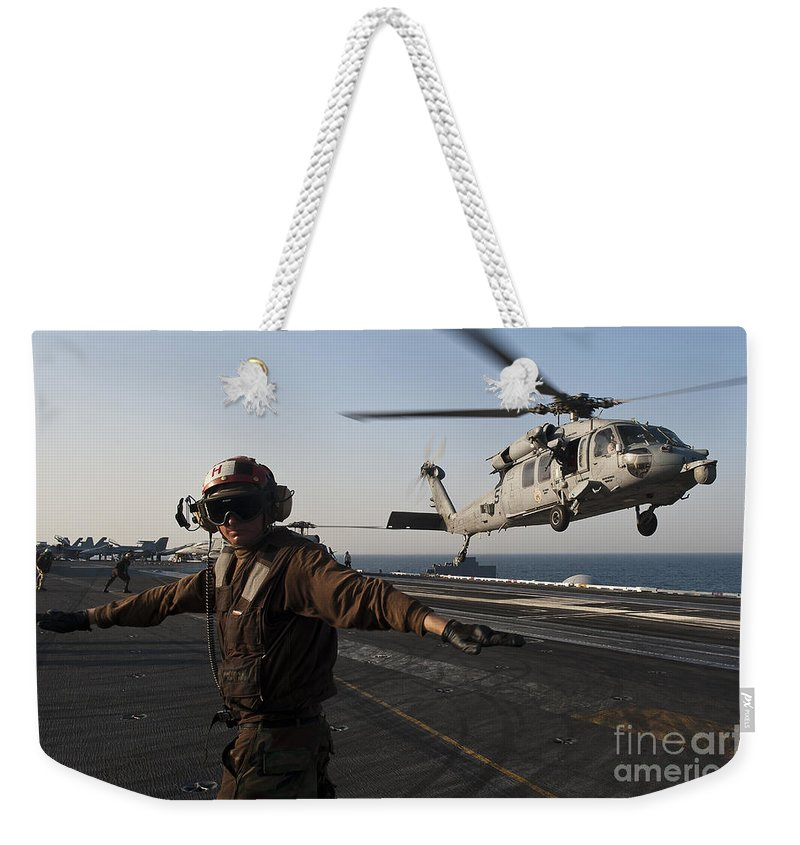 Operation New Dawn Weekender Tote Bag featuring the photograph Airman Checks For A Clear Deck As An by Stocktrek Images