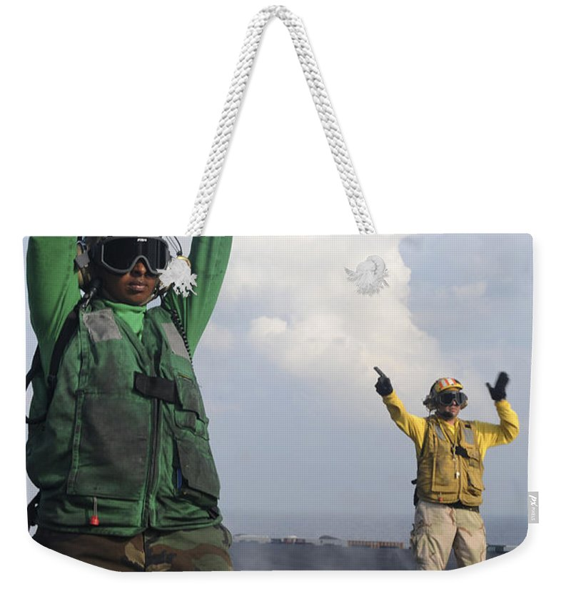 Uss John C Stennis Weekender Tote Bag featuring the photograph Airmen Communicate To Aircraft Aboard by Stocktrek Images