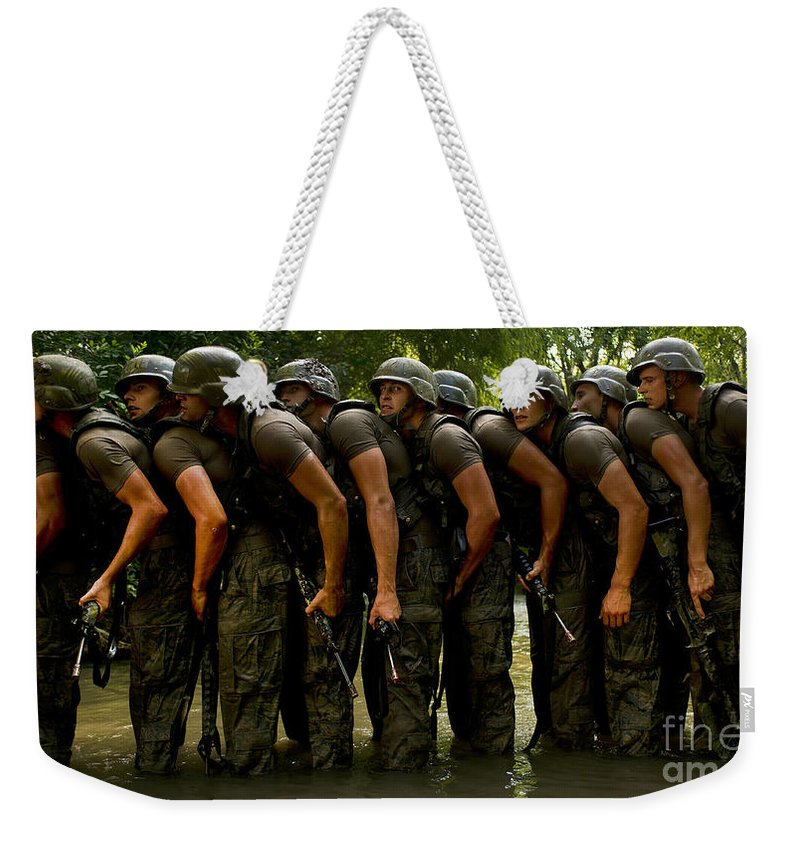 Toughness Weekender Tote Bag featuring the photograph Airmen Stack Up In A Pond by Stocktrek Images