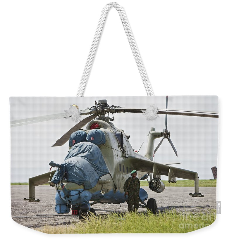 Mil Mi-35 Weekender Tote Bag featuring the photograph An Afghan Army Soldier Guards A Mi-35 by Terry Moore