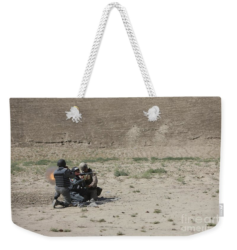 Kunduz Weekender Tote Bag featuring the photograph An Afghan Police Studen Fires by Terry Moore