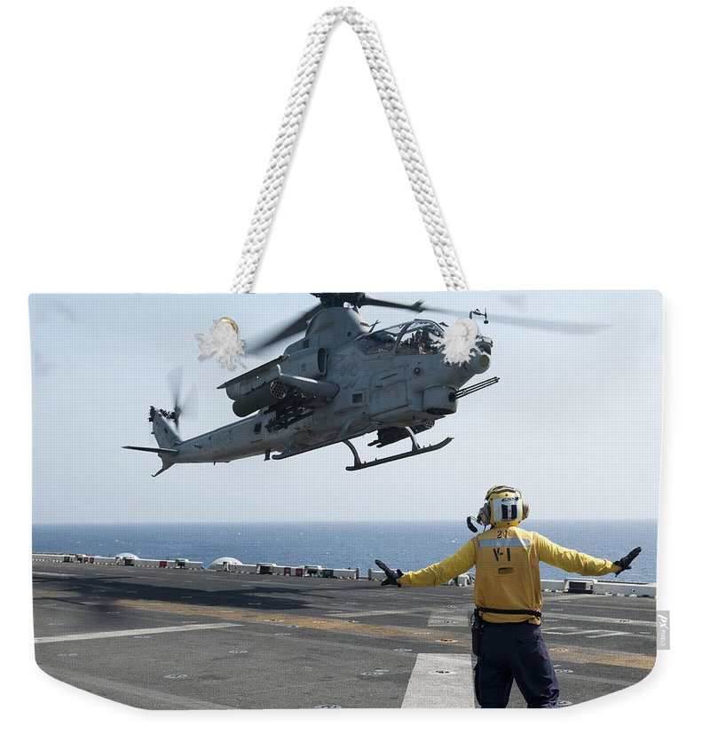 Uss Makin Island Weekender Tote Bag featuring the photograph An Ah-1z Cobra Helicopter Takes by Stocktrek Images