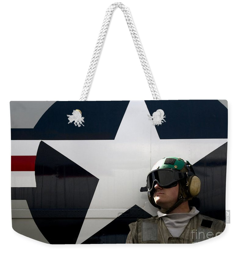 Uss Carl Vinson Weekender Tote Bag featuring the photograph An Airman Stands In Front Of A C-2a by Stocktrek Images