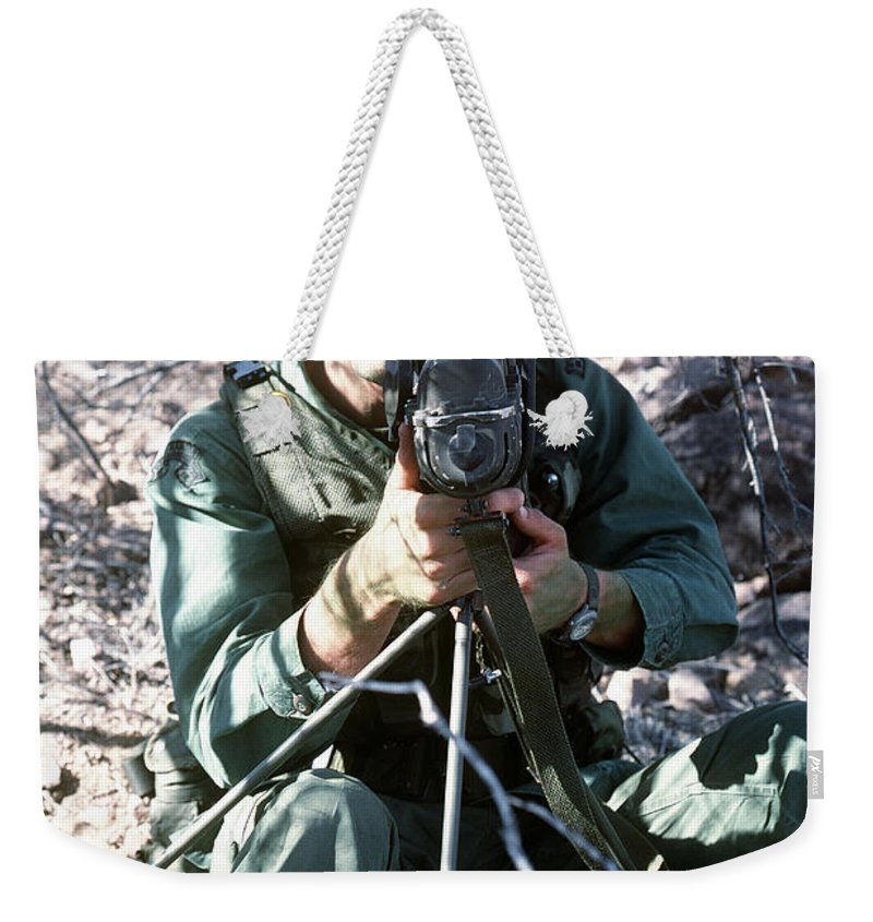 Military Weekender Tote Bag featuring the photograph An Army Ranger Sets Up An Anpaq-1 Laser by Stocktrek Images