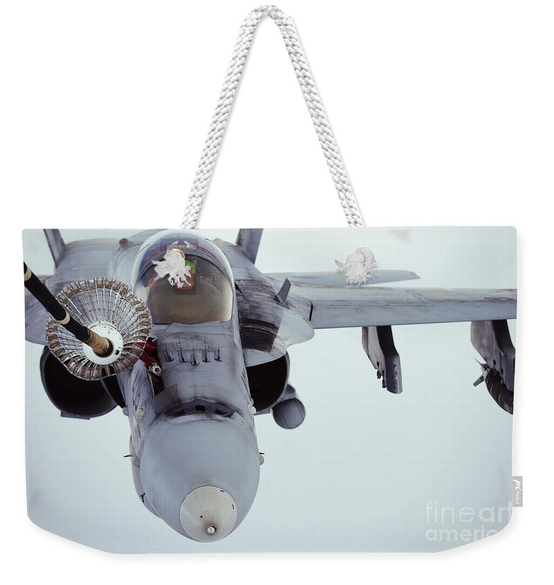 Kc-10 Extender Weekender Tote Bag featuring the photograph An Fa-18 Super Hornet Receives Fuel by Stocktrek Images