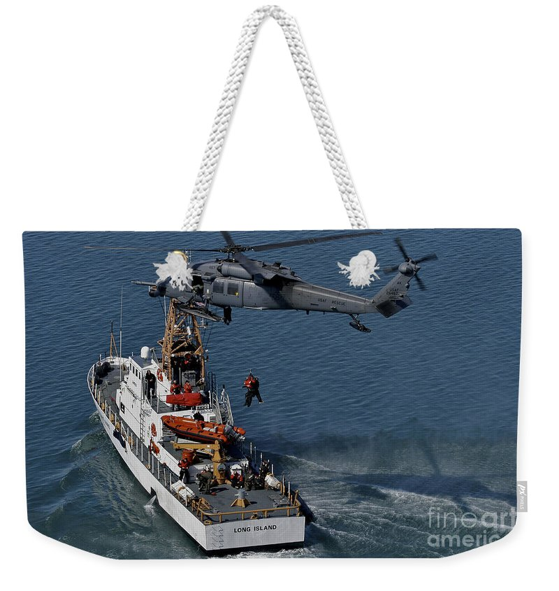Military Weekender Tote Bag featuring the photograph An Hh-60g Pave Hawk Performs A Hoist by Stocktrek Images