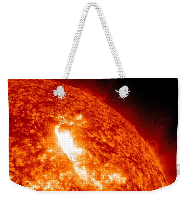 Solar Energetic Particles Weekender Tote Bag featuring the photograph An M8.7 Class Flare Erupts On The Suns by Stocktrek Images
