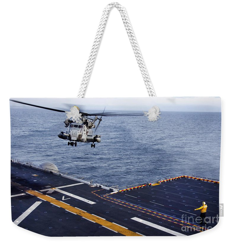 Pacific Ocean Weekender Tote Bag featuring the photograph An Mh-53e Sea Dragon Prepares To Land by Stocktrek Images