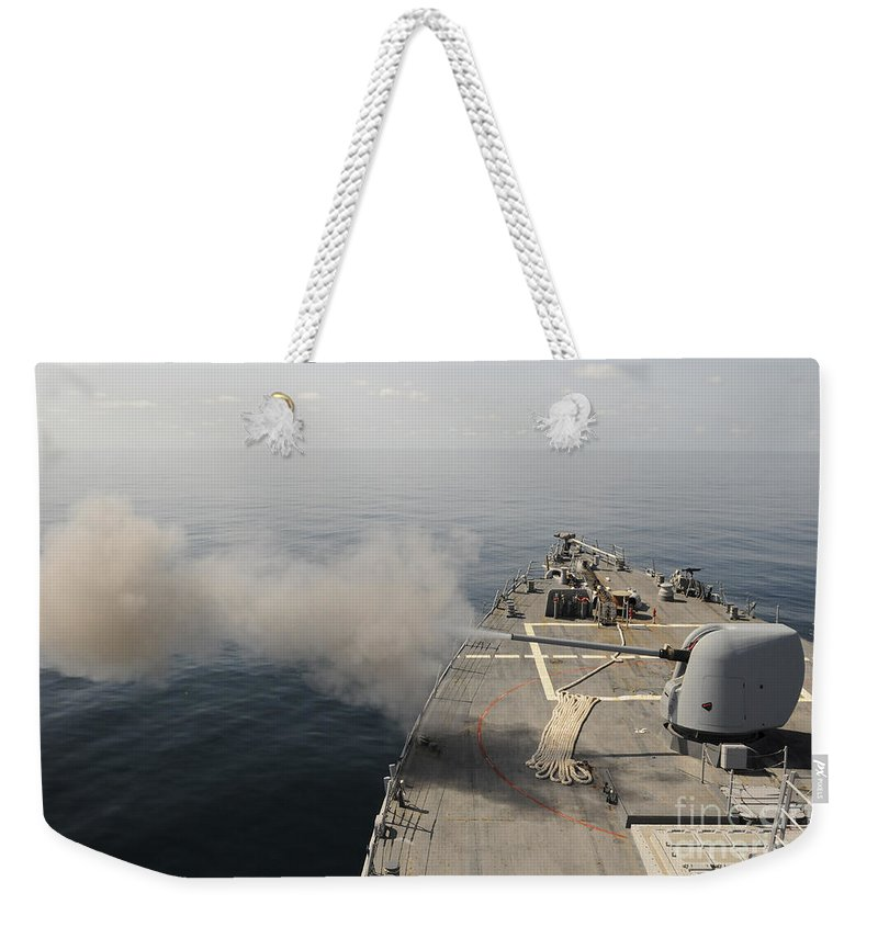 Guided Missile Destroyers Weekender Tote Bag featuring the photograph An Mk-45 Lightweight Gun Is Fired by Stocktrek Images