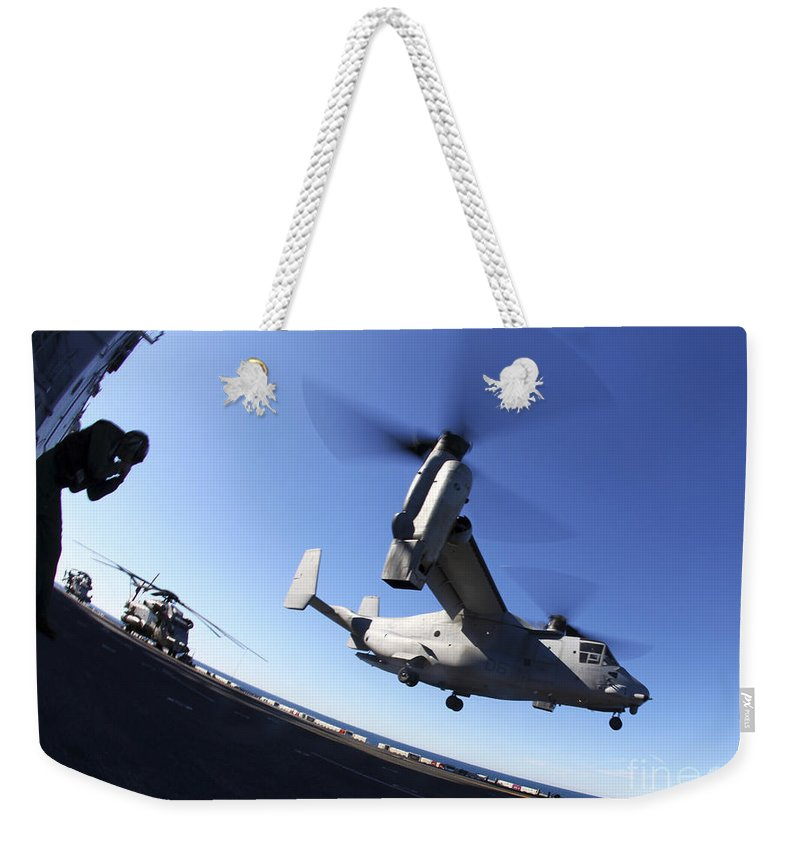 Warship Weekender Tote Bag featuring the photograph An Mv-22 Osprey Lands Aboard The Uss by Stocktrek Images