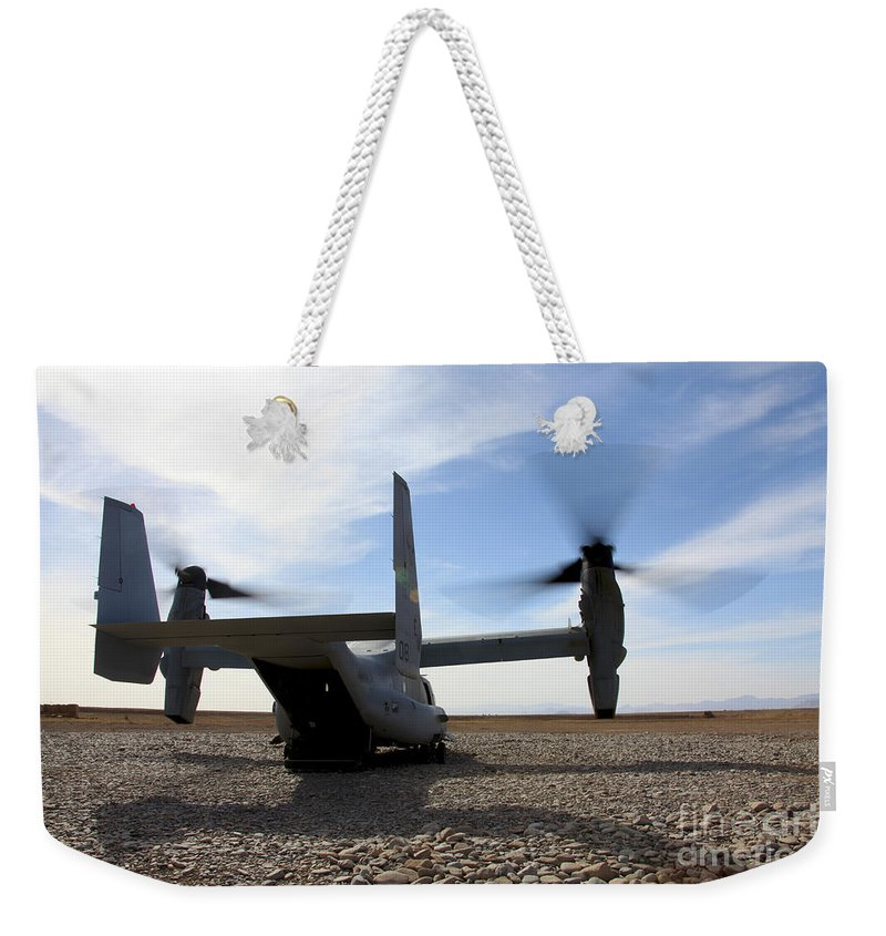 Mv-22 Weekender Tote Bag featuring the photograph An Mv-22 Osprey Sits Outside A Forward by Stocktrek Images